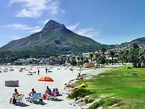 The glorious white sandy beach for which Camps Bay is famous, looking towards Signal Hill.  Find Camps Bay Capetown accommodation with its beaches and sunshine on our Camps Bay Cape Town accommodation page.
