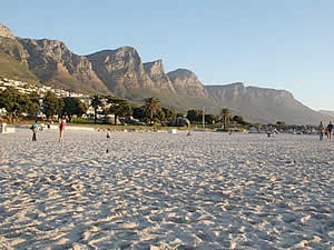 Camps Bay beach looking south at the Twelve Apostles mountain range.  Find Camps Bay Capetown accommodation with its beaches and sunshine on our Camps Bay Cape Town accommodation page.